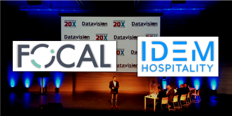 E20X Mallorca stage with Lyle Worthington presenting. IDEM Hospitality logo and Focal Revenue Solutions Logo.